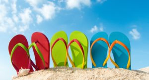 Row of colorful flip flops on beach against sunny sky